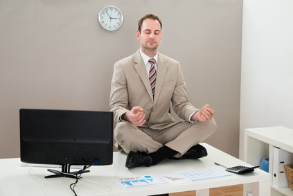 Businessman Sitting On The Desk And Meditating With Eyes Closed