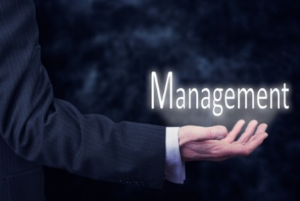 The arm of a businessman holding the word Management.